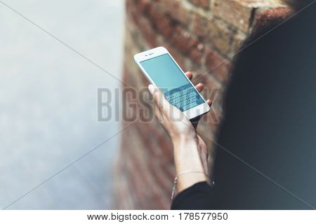 Women using blank smartphone isolated hipster manager holding mobile girl texting message sms connect concept blur background brick mockup female hands touch digital screen user social network
