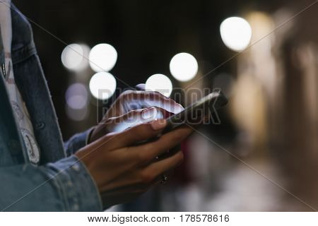 Girl pointing finger on screen smartphone on background illumination bokeh color light in night atmospheric city hipster using in female hands and texting mobile phone mockup glitter street content lifestyle