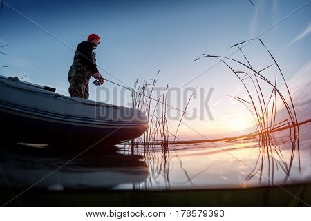 Split shot of a man fishing from the boat on the lake at sunset