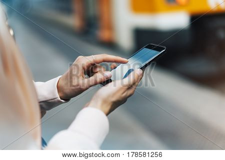 Enjoying travel. Young pretty woman waiting on the station platform with backpack on background electric train using smartphone. Tourist texting message and plan route of railway railroad transport concept