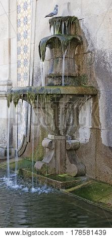 Old large weathered water fountain in portugal