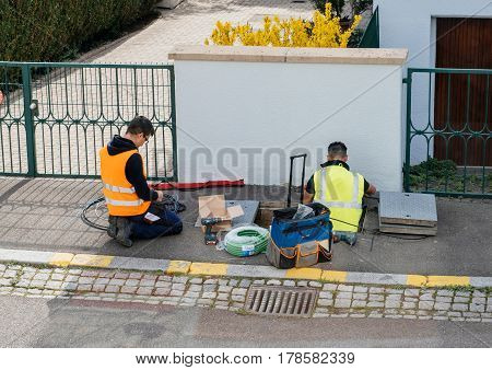 PARIS FRANCE - MAR 24 2017: Team of workers from telecomunication internet provider company working on implementation of fiber optic cables in sewage system - aerial view