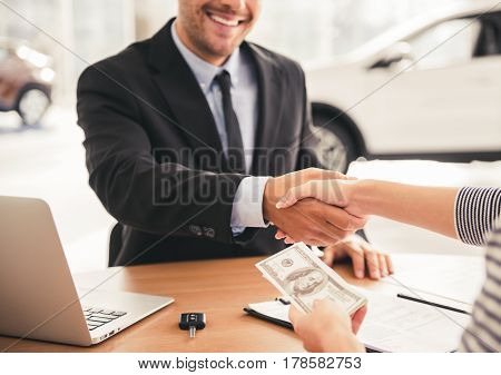 Visiting car dealership. Handsome sales manager is shaking hand with a client and smiling