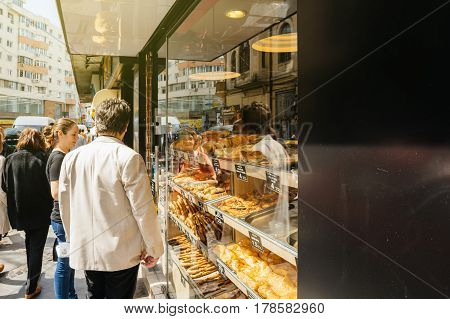 BUCHAREST ROMANIA - MAR 21 2016: Customers admiring selection of typical street food in Bucharest Romania bakery selling placinte other pastries with customers waiting the hot and delicious food