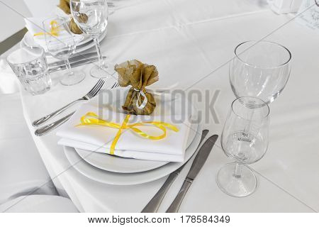 served wedding table. on the table is a plate knife wine glasses a towel a gift