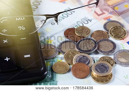 Closeup of glasses on euro banknotes with coins and calculator. Business concept.