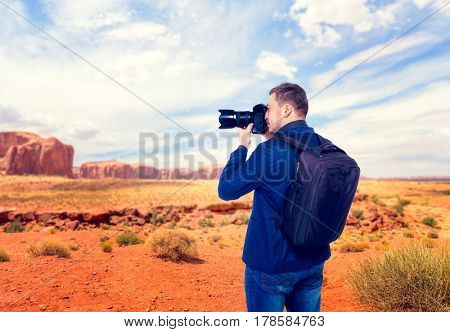 Male traveler photographing mountain valley
