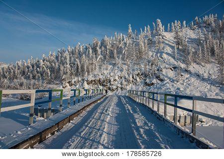 Bridge of Kolyma highway on the winter mountains background