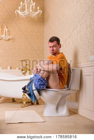 Constipation problem, man sitting on toilet bowl