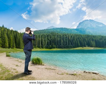 Male photographer taking picture of lake on camera