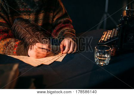 Male hands writes with a feather on vintage paper