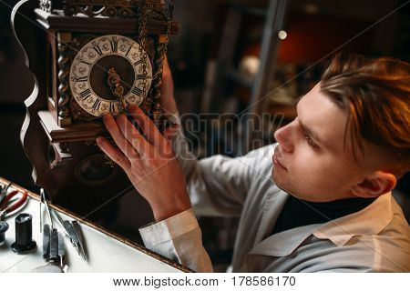 Watchmaker adjusts the mechanism of old watches
