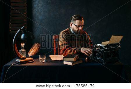 Writer in glasses typing on vintage typewriter