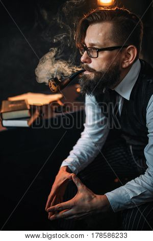 Serious bearded man in glasses smoking pipe