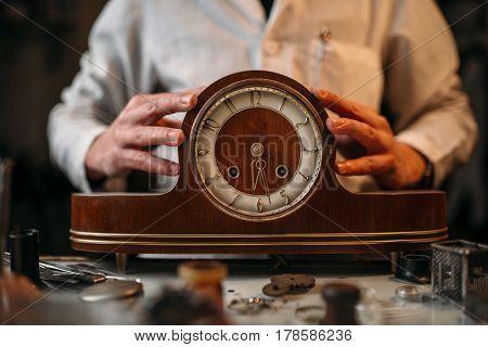 Watchmaker restore old wooden table clock