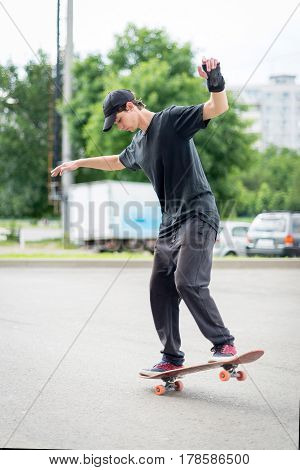 Teenage skateboarder with hand protection standing on skateboard, balances