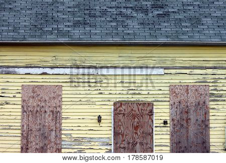 Closeup of Boarded Up and Abandoned Yellow House