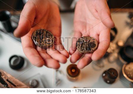 Watchmaker hands with clockwork mechanism closeup