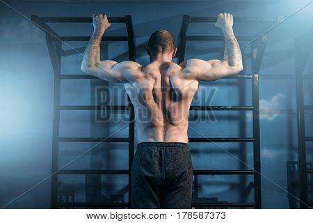 Strong sportsman training on horizontal bar in gym