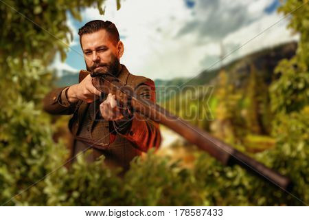 Hunter sitting in the bushes and aiming a rifle.