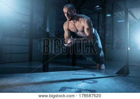 Muscle athlete makes pushups exercises in gym