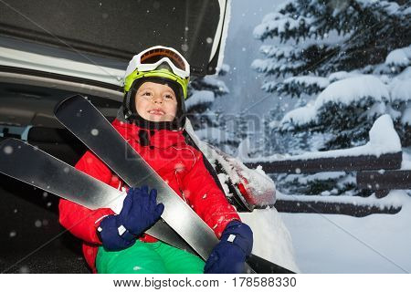 Close-up portrait of happy boy holding skis and sitting in the car trunk during snowfall