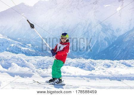 Portrait of kid boy going uphill in the mountains using a surface lift on the slope