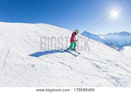 Portrait of little skier with safety helmet, goggles and poles, walking down the hill at sunny snowy day