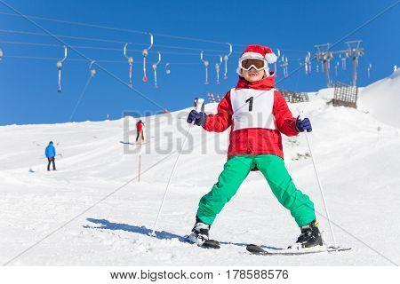 Cute little boy in Santa's hat learning to ski in  alpine resort in wintertime