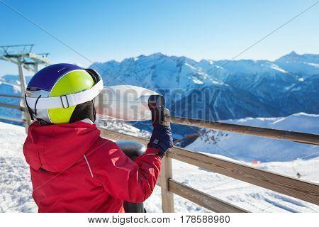 Little skier looking through binoculars on the snowy mountain scenes