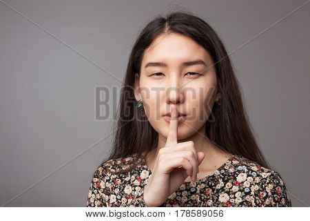 Asian Beautiful Girl With Long Hair Shows A Sign Of Silence. The Index Finger At The Mouth.