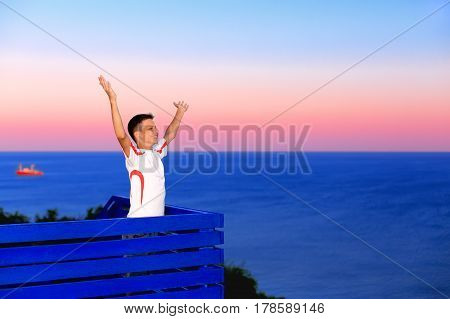 Happy boy with arms open to the sky against the sea at sunset