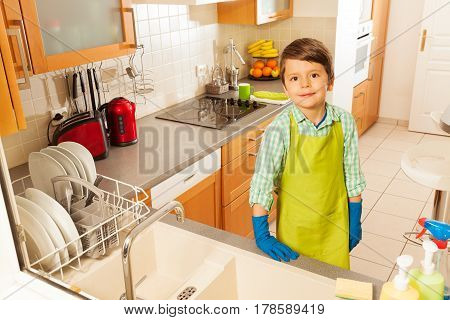 Little boy standing near kitchen sink wearing apron and protective gloves after washing dishes