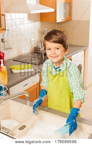 Young smiling little boy washing dishes in the kitchen with a lot of soap in the sink