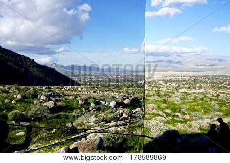 mirrored wall reflecting the desert landscape around it