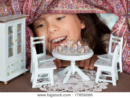 Alice in wonderland looking into a dollhouse