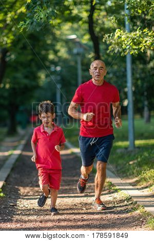 Grandfather and grandson jogging in park, color image