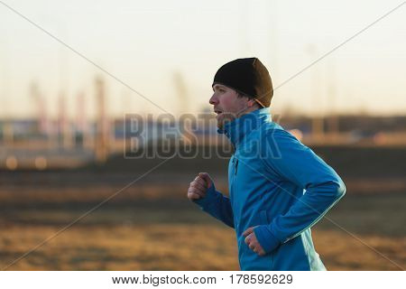 A Young Man In A Hat And Blue Clothes Runs In The Morning On The Background Of Factory Pipes And Smo