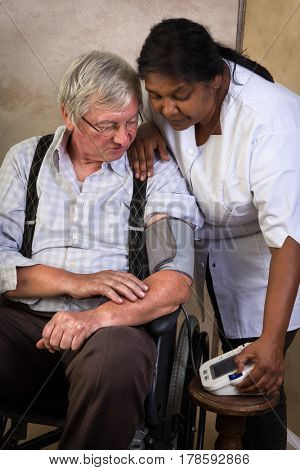 Nurse measuring blood pressure of an elderly man in a wheelchair