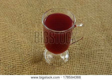 Cherry juice cider in glass on burlap