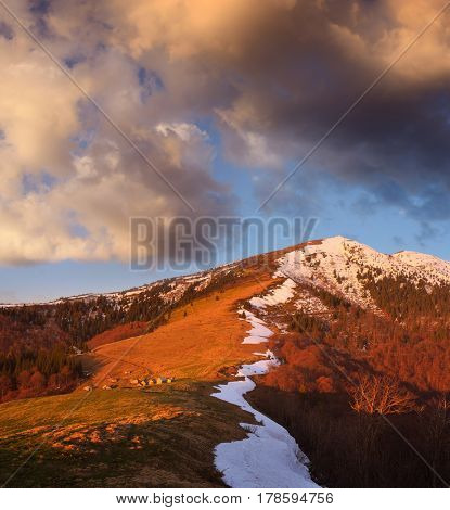 Spring landscape with wooden houses in the mountains. Settlement of the shepherds. Light of the setting sun