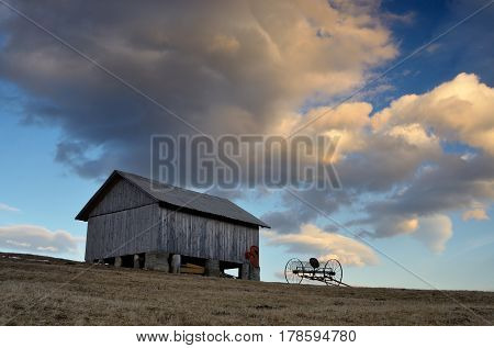 Spring in a mountain village. A wooden shed on a hill. The sky with beautiful clouds