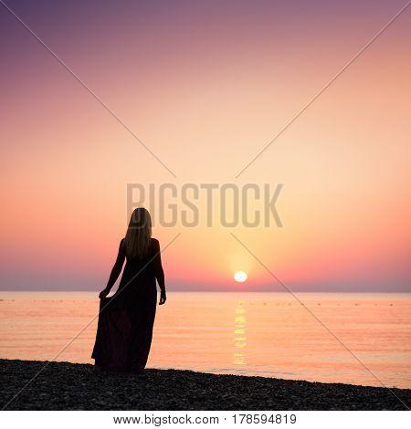 Blonde girl standing on the beach. Beautiful sunrise. Activities at the resort. Sea vacation. Turkey