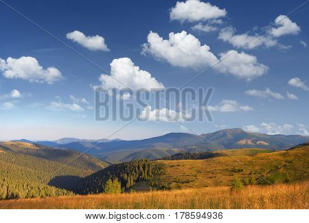 Autumn landscape in the mountains. Sky with beautiful clouds. Sunny day