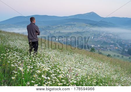 Tourist is standing in a mountain meadow and looking at the peaks. Summer landscape with flowers in village. Morning fog. Carpathians, Ukraine, Europa