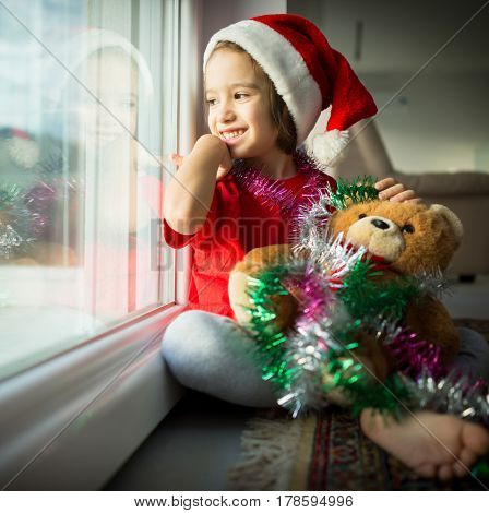 Child in warm house looking trough window at winter landscape