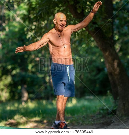 Senior Male Exercising Outdoors In Public Park