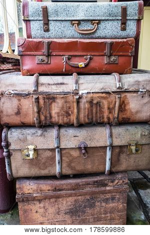 A pile of old and worn antique suitcases.
