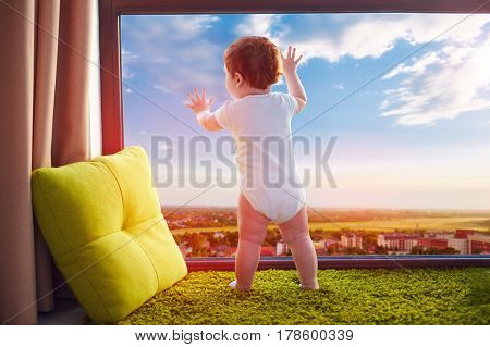 Infant Baby Watching The Beautiful Valley Cityscape Through The Window At Home