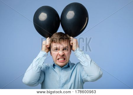 Young Angry Man Holding Black Balloons In The Head, Ape. Bad Mood At The Party.